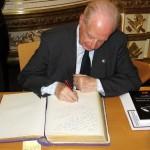 El padre Ceballos firma el libro de visitas