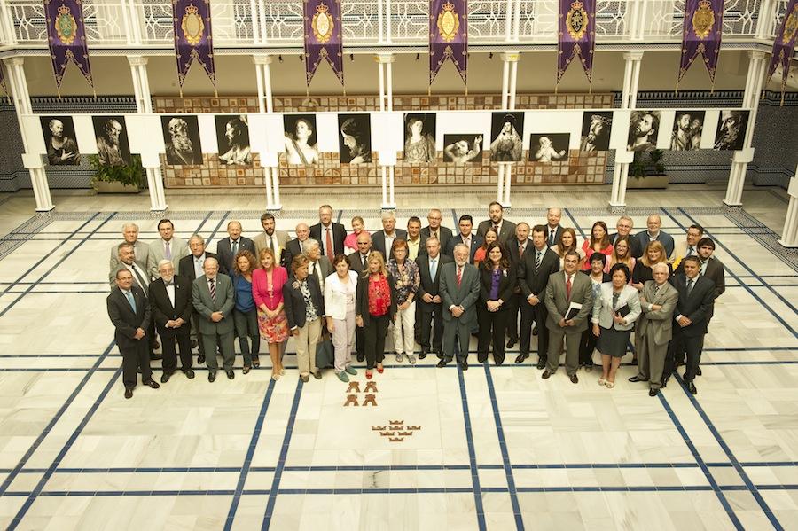 Los diputados de todos los grupos políticos posan junto a los representantes de la Cofradía de Jesús, entre los que se encuentran algunos de los funcionarios de la propia Asamblea, que son mayordomos, estantes y cabos de andas de la misma